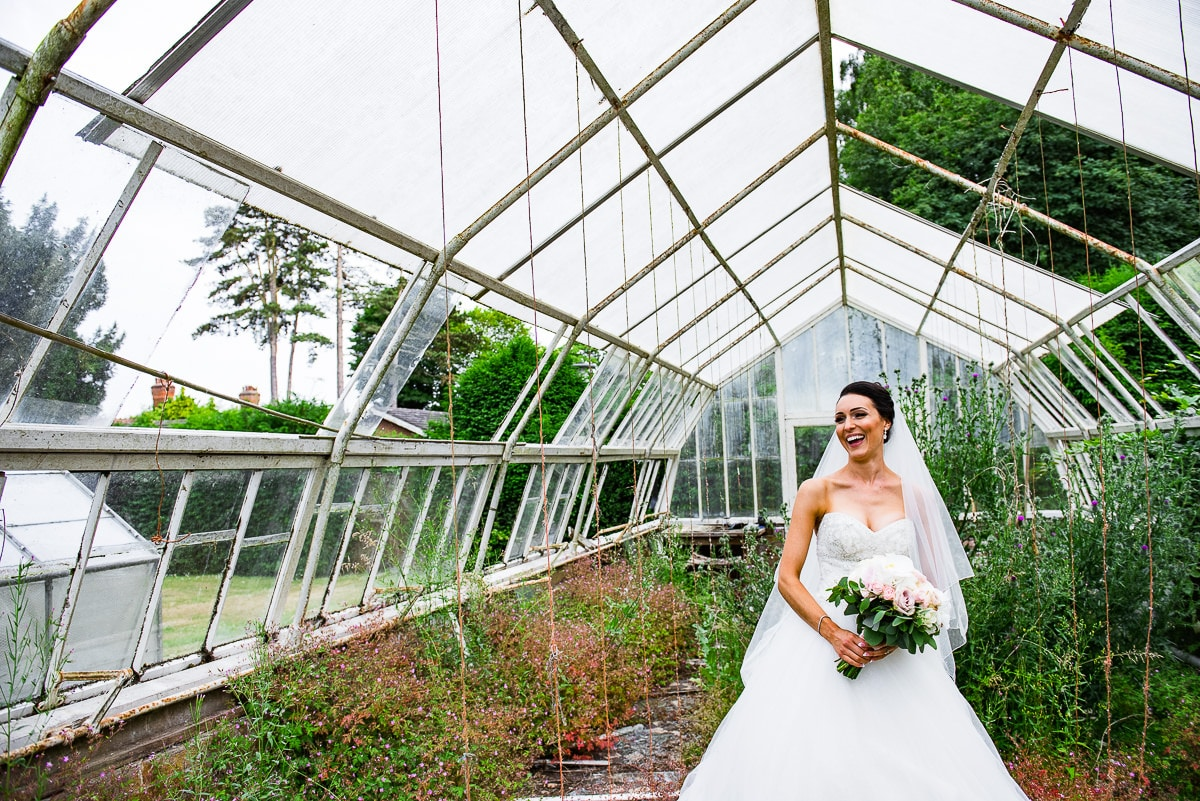 Bride holding bouquet in rustic greenhouse at best Countryside Wedding Venue