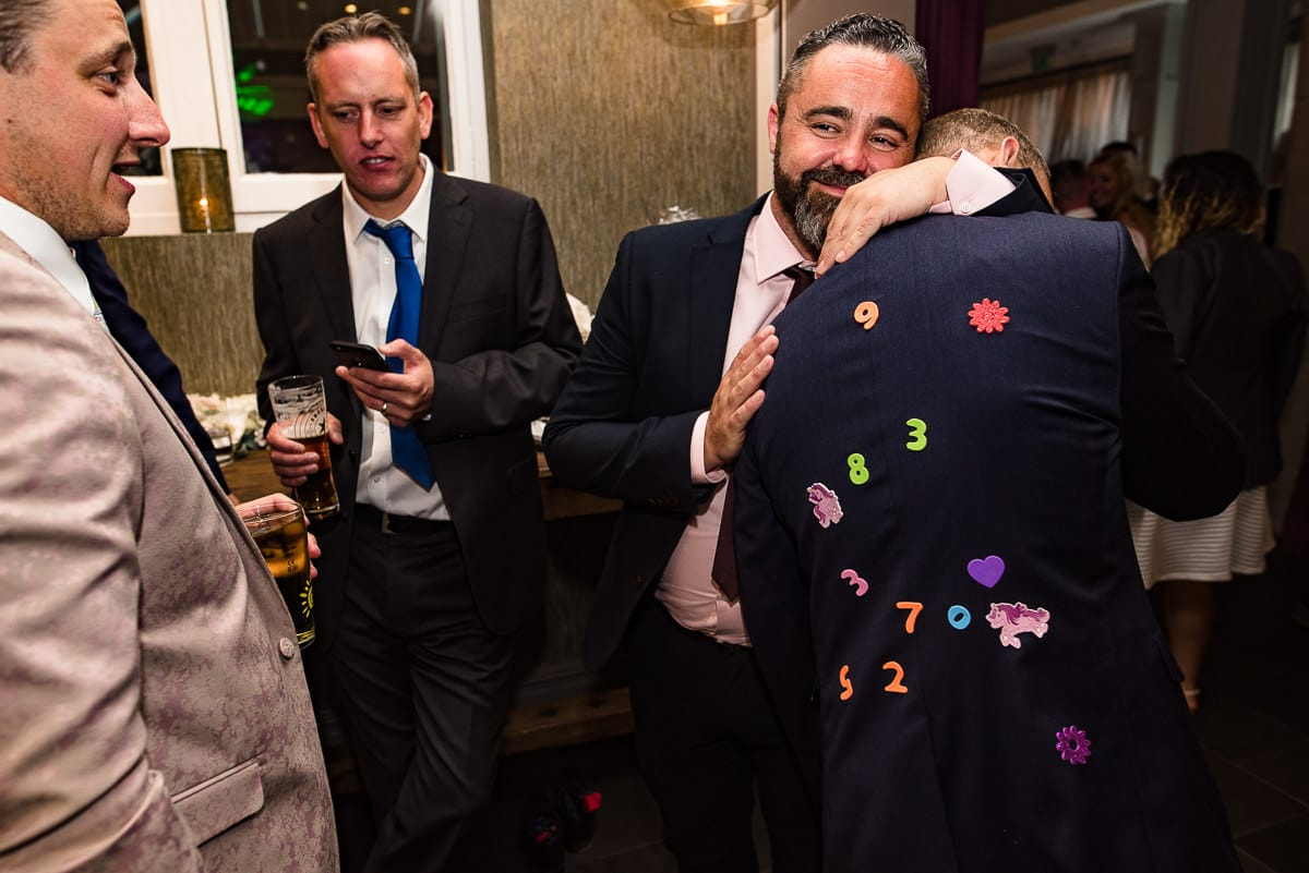 Wedding guest covered in children's stickers on his suit hugs mate