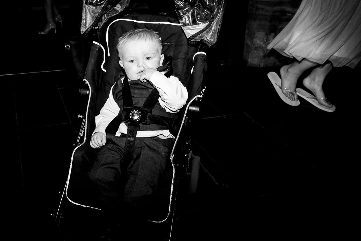 baby in pushchair picking his nose at wedding