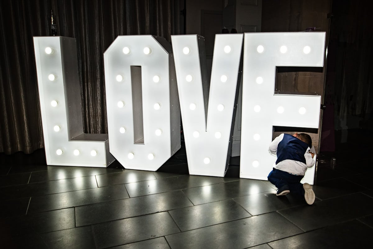 Giant light lettering love with young boy exploring