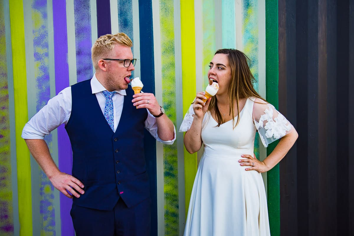 bride and groom lick ice cream in front of colourfully painted wall