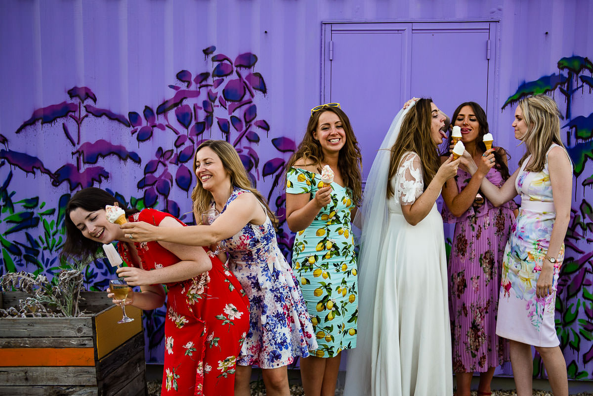 Wedding guests wearing colourful floral dresses enjoy ice cream