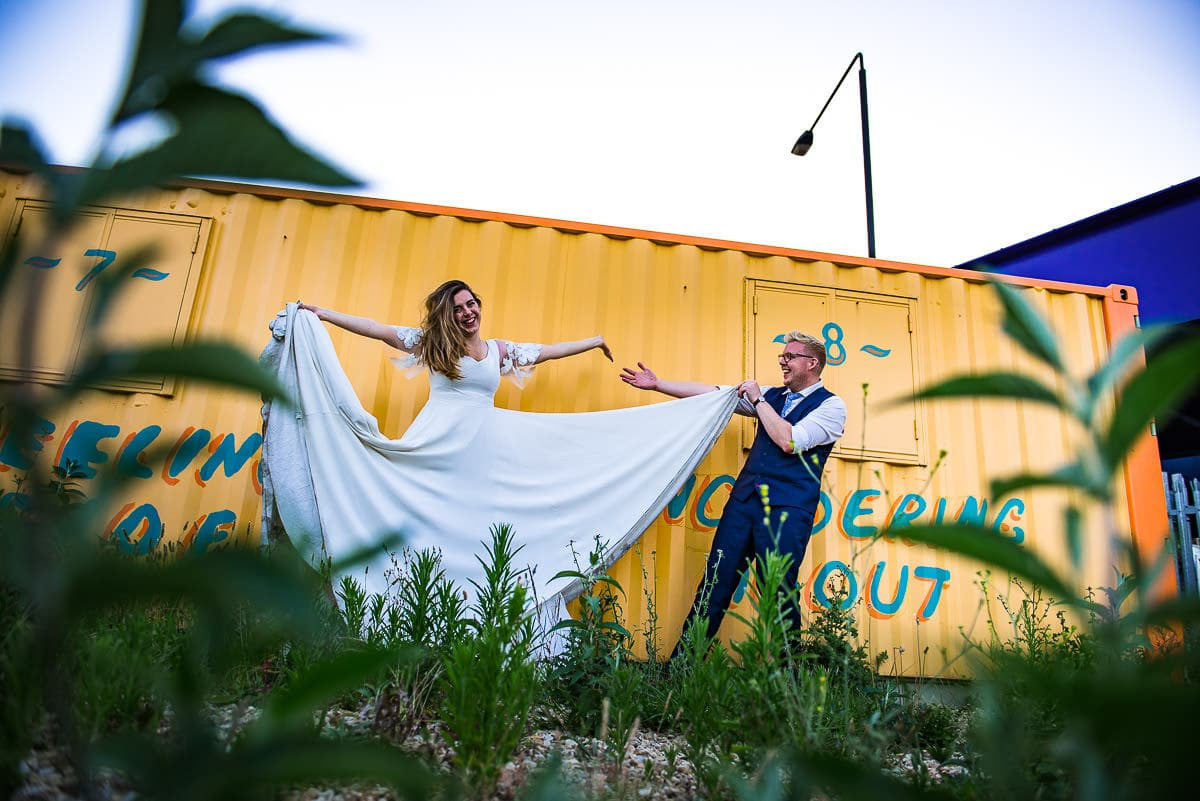 groom and bride show off wedding dress by yellow shipping container