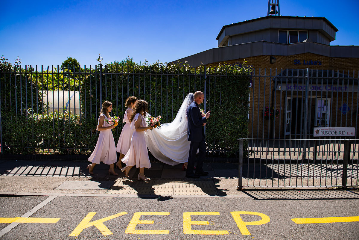 bridesmaids hold the brides veil as they walk down London street