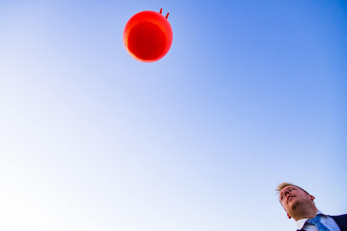 Orange space hopper thrown into the air against blue sky