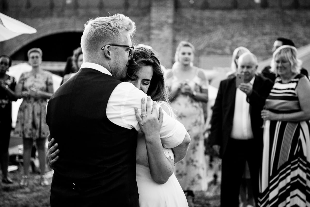 bride and groom embrace for first dance outside London venue