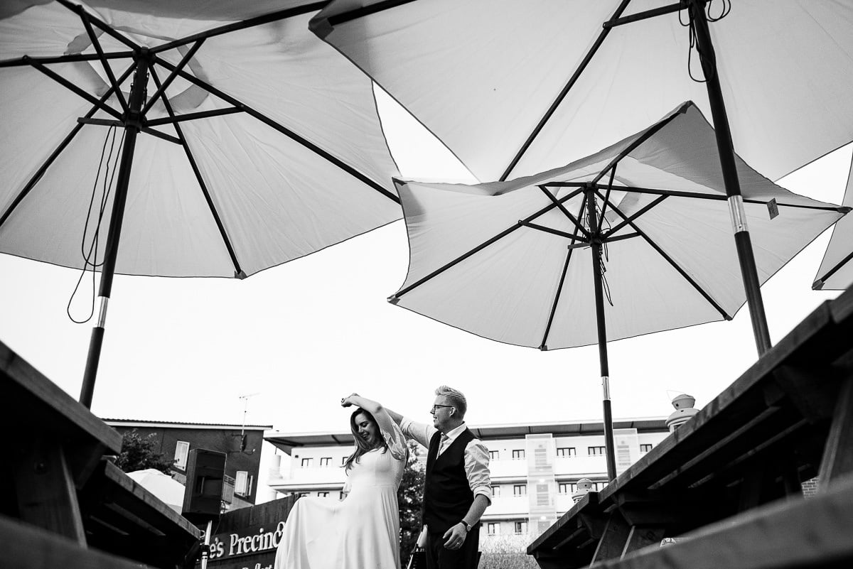 bride and groom dance under London pub umbrellas
