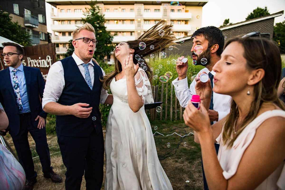 bride and groom dance and sing as wedding guests blow bubbles