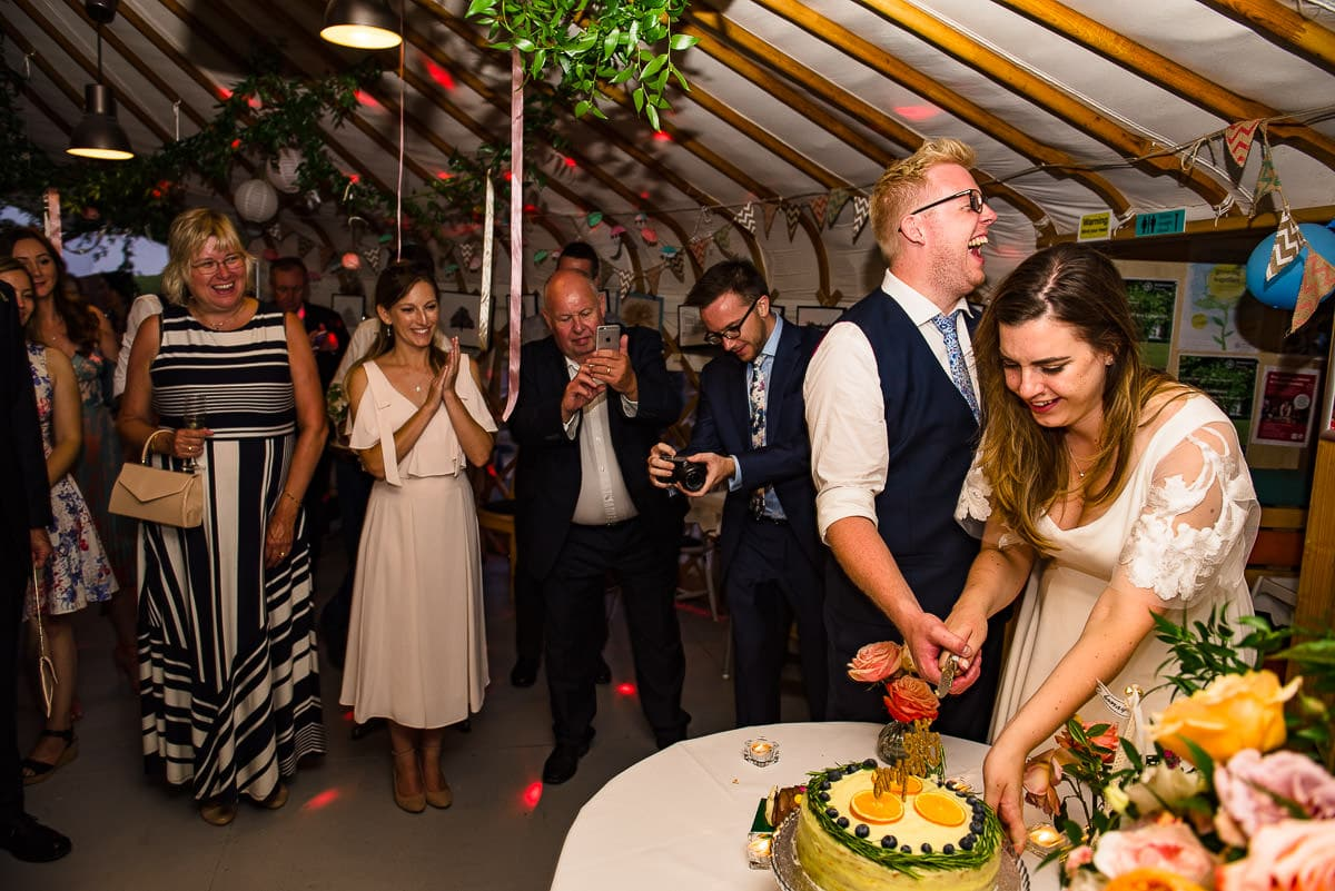 bride and groom cut cake inside alternative London yurt wedding venue
