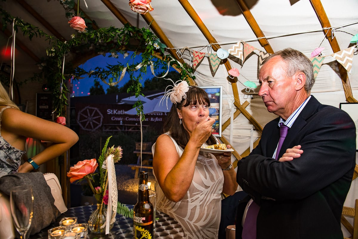 wedding guests tuck into cake at the yurt party