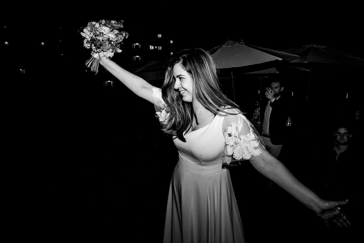 bride holds bouquet of flowers aloft