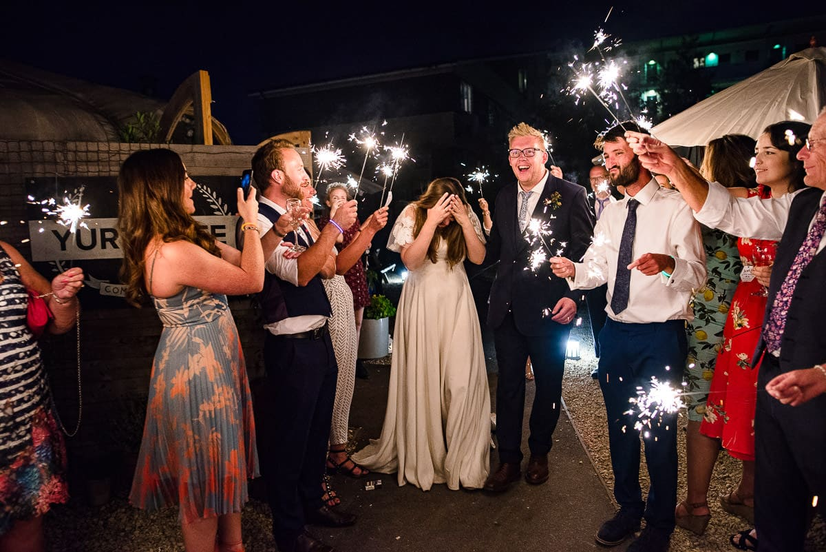 wedding guests celebrate marriage with sparklers at night exit