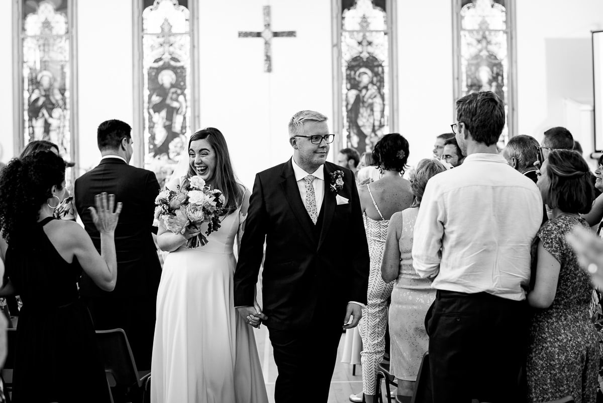 Bride and groom walk back down the church aisle