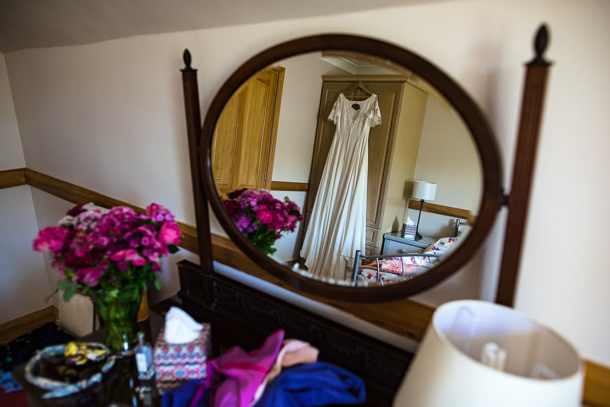 Hanging wedding dress reflecting in bedroom dressing mirror