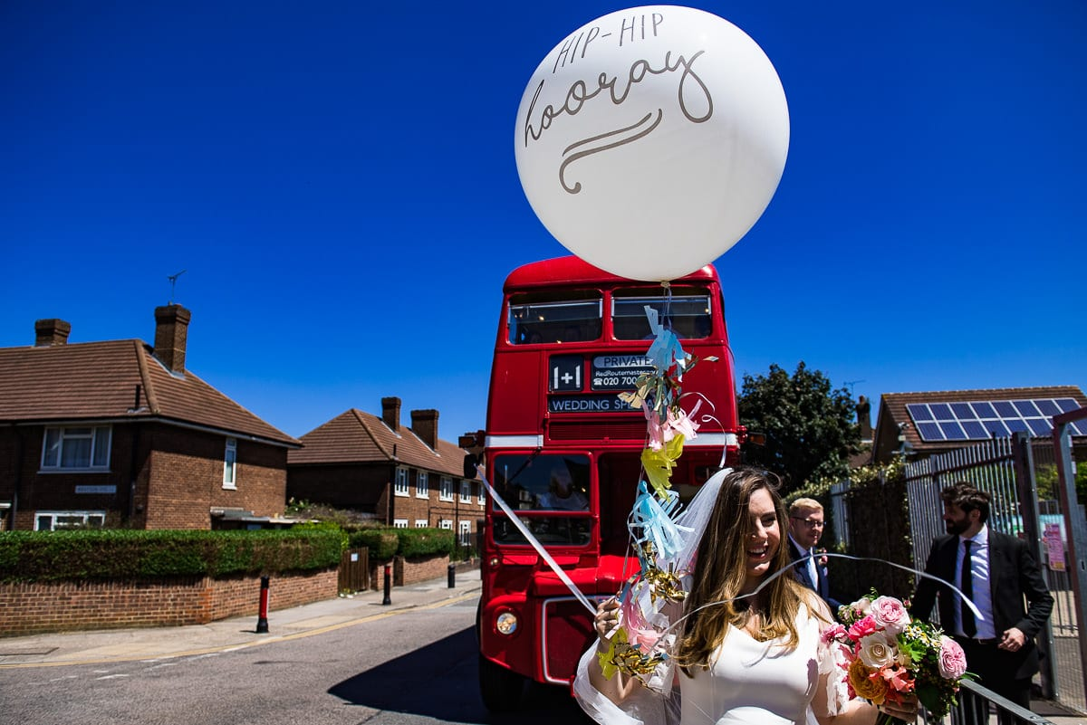 bride with big balloon by wedding bus provided by red route master