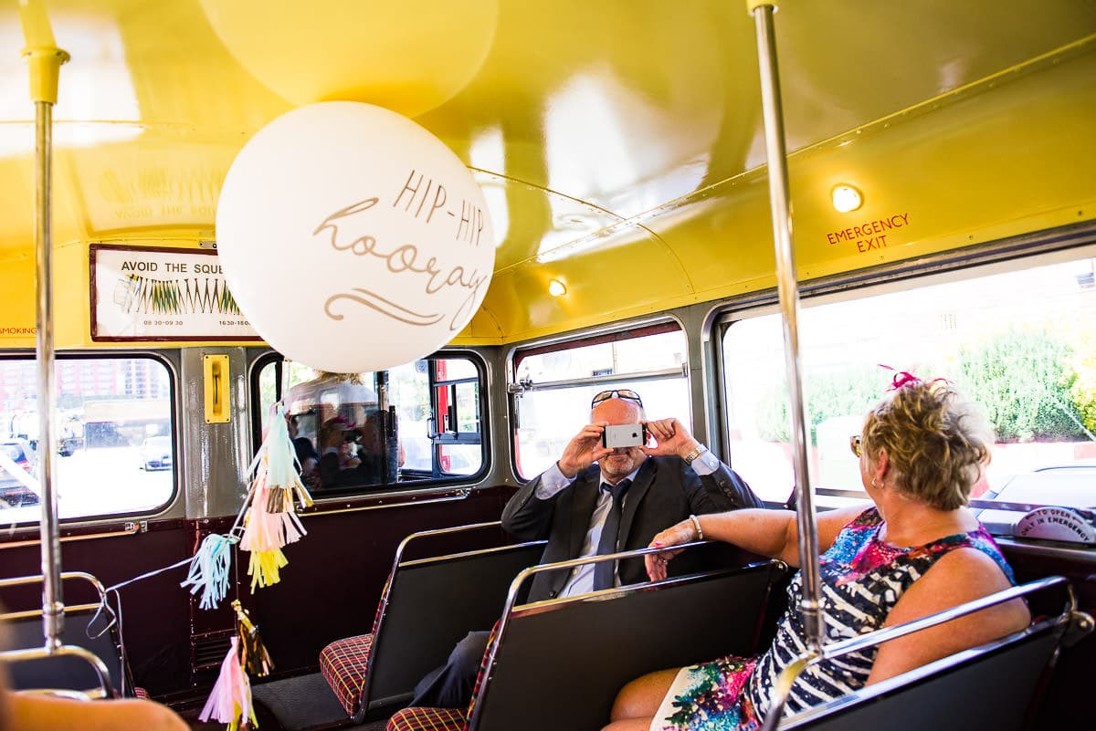 guests take photos on the colourful London wedding bus