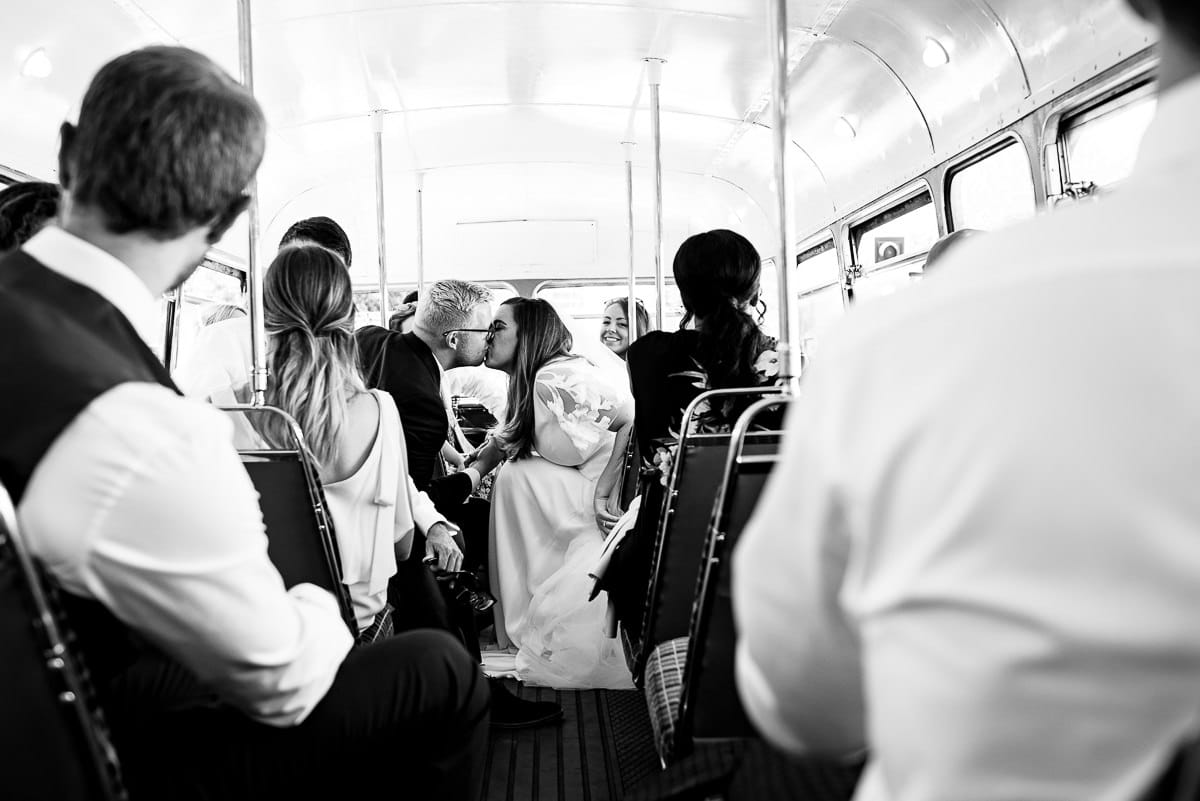 bride and groom kiss as guests sit aboard the London Route master bus