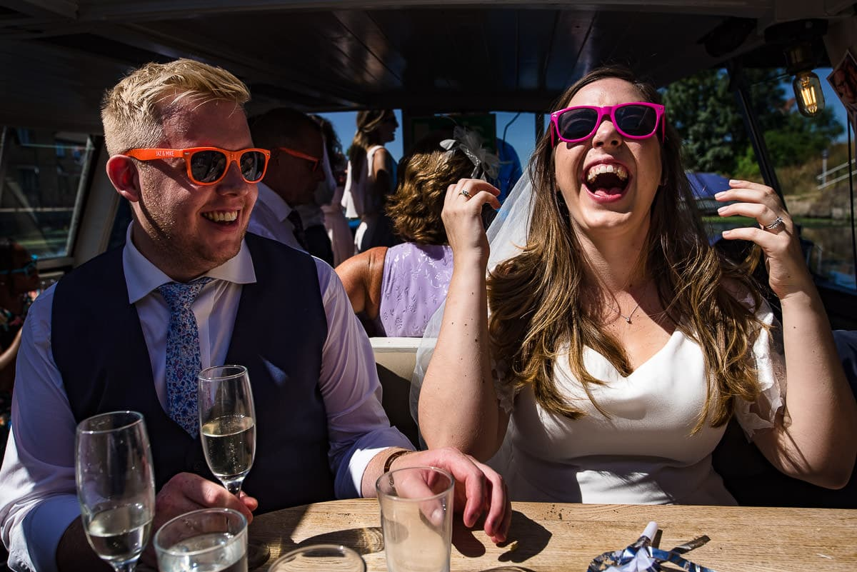 bride and groom laughing on board with colourful sunglasses
