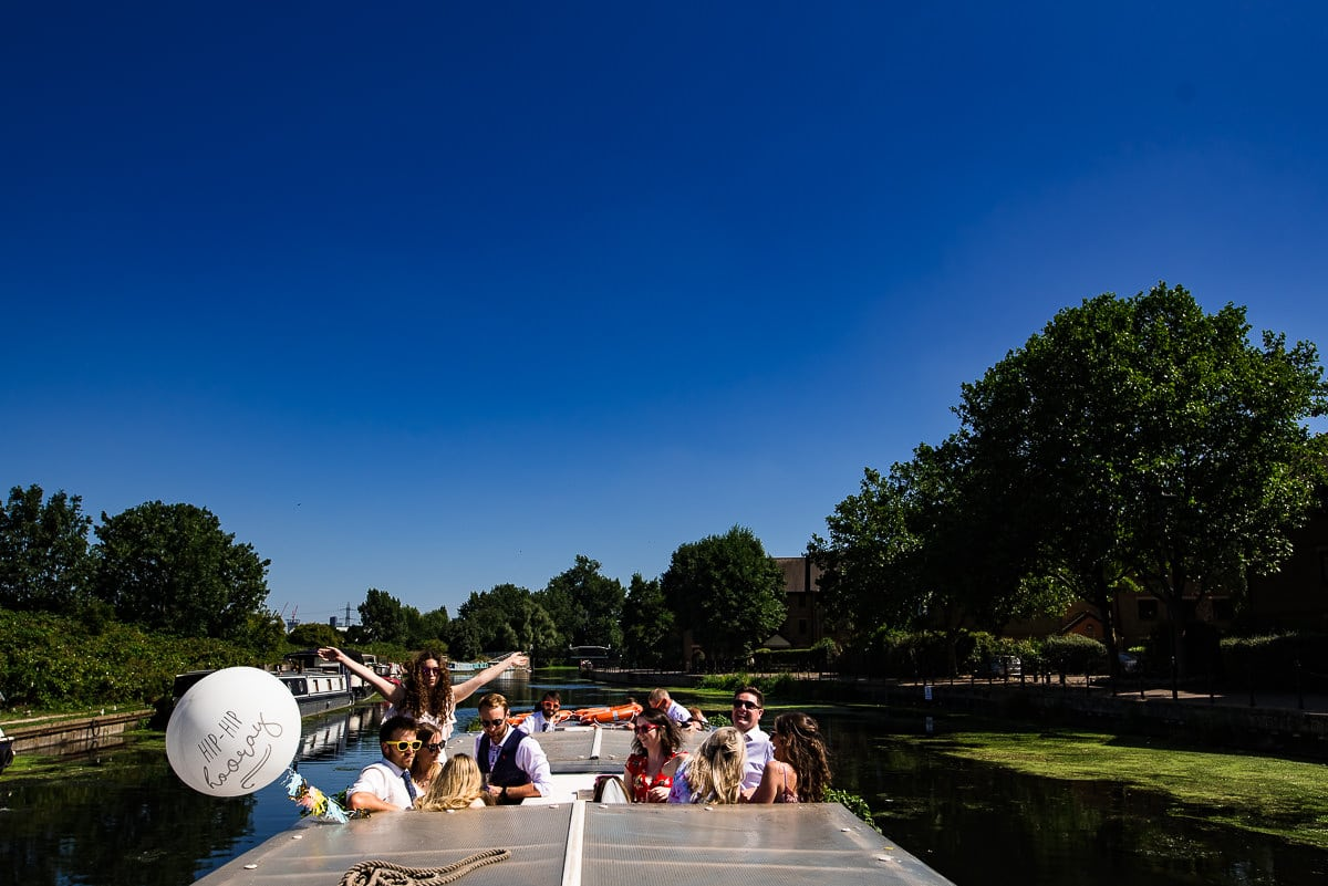 London wedding guests enjoy the sun out on the roof of the canal boat