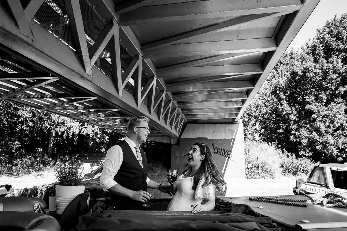 bride and groom joke around as the boat goes under bridge