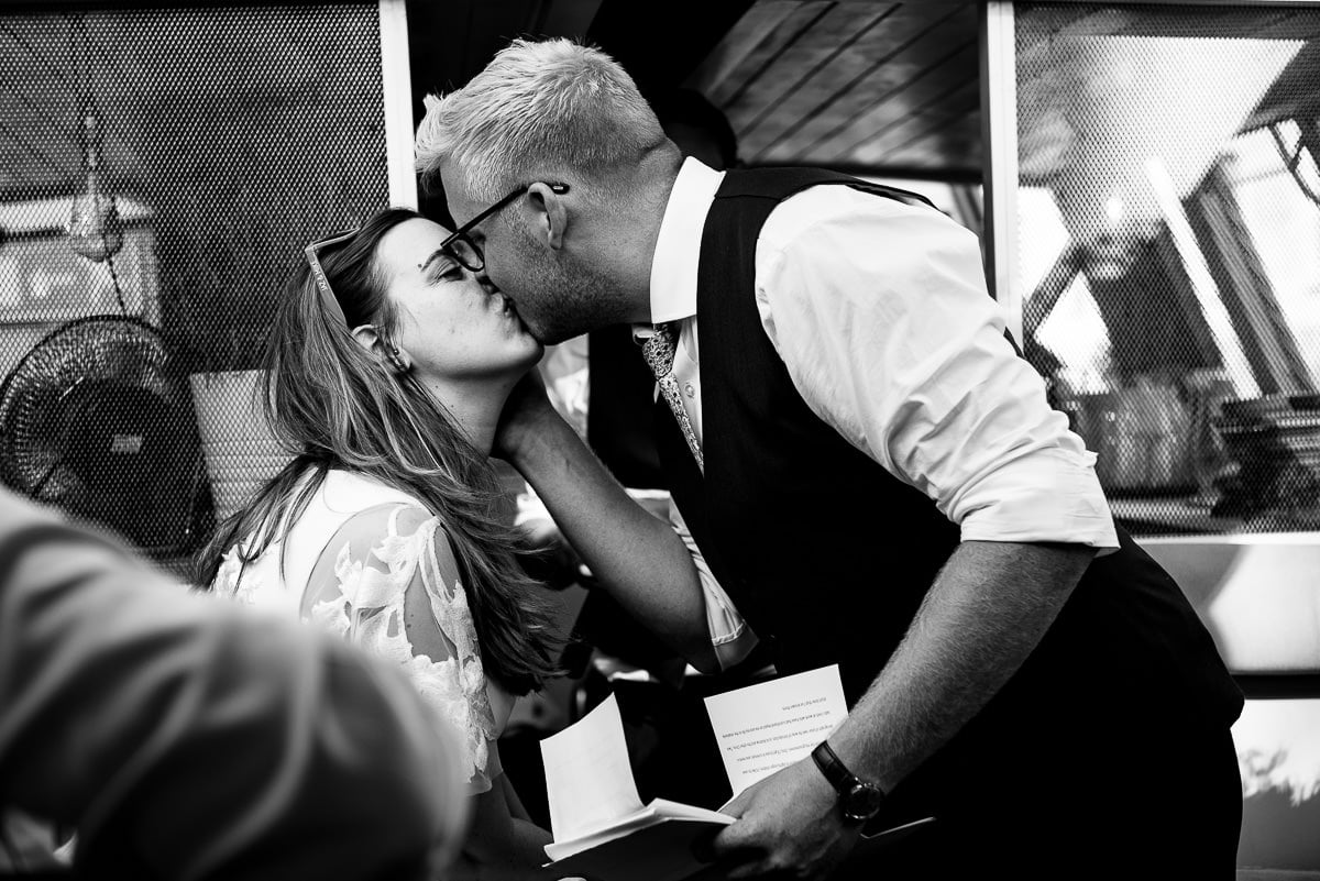 bride and groom kiss on Alfred Le Roy party boat