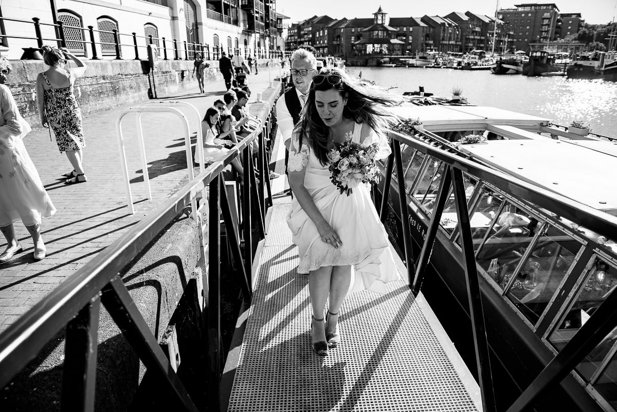 bride and groom walk off the boat in London dockyard