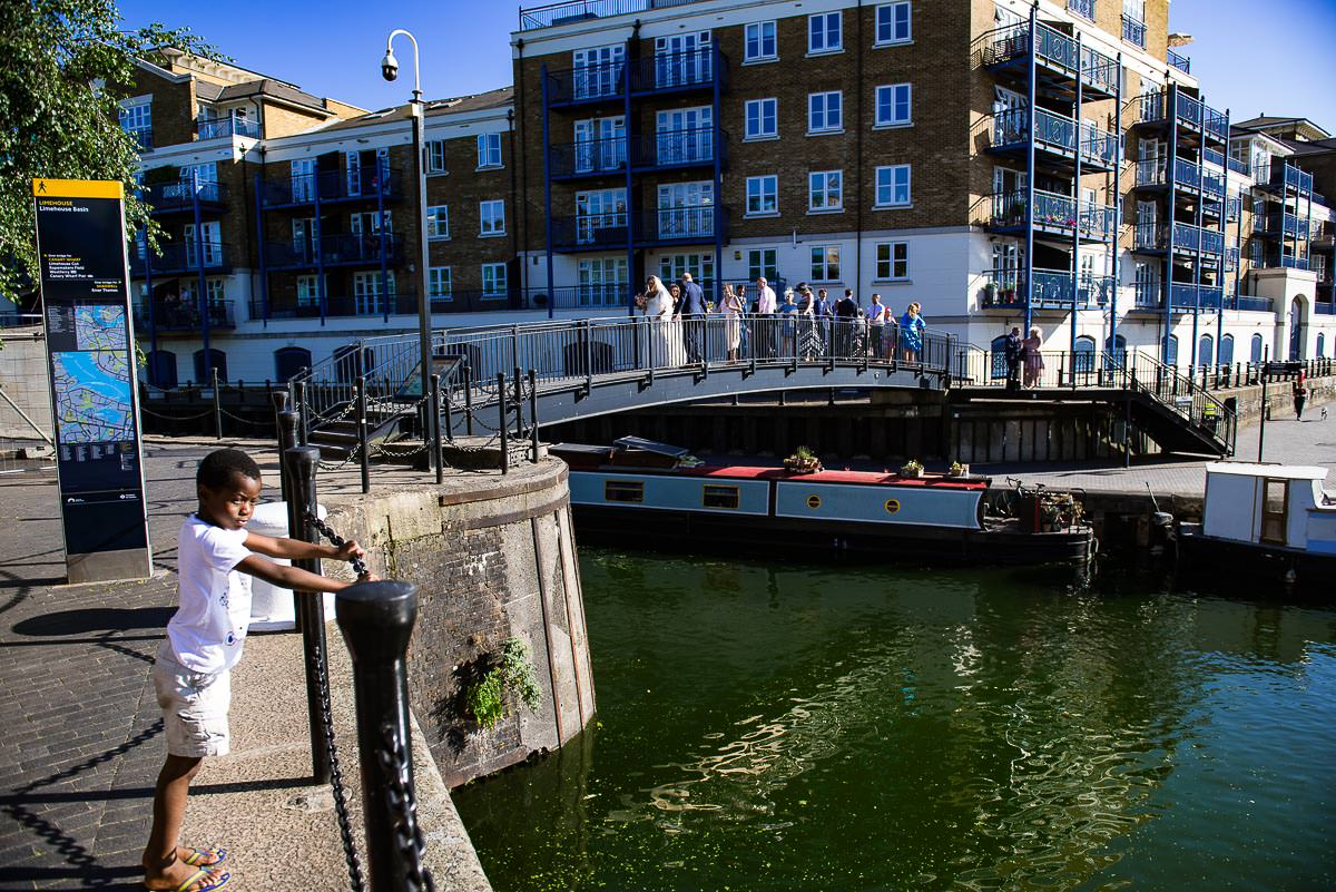 wedding guests walk over London dockyard bridge canal in the sun