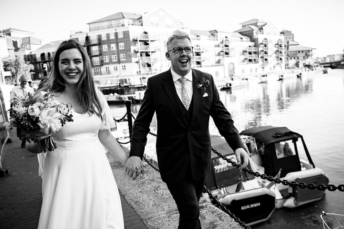 bride and groom stroll holding hands by the canal in London