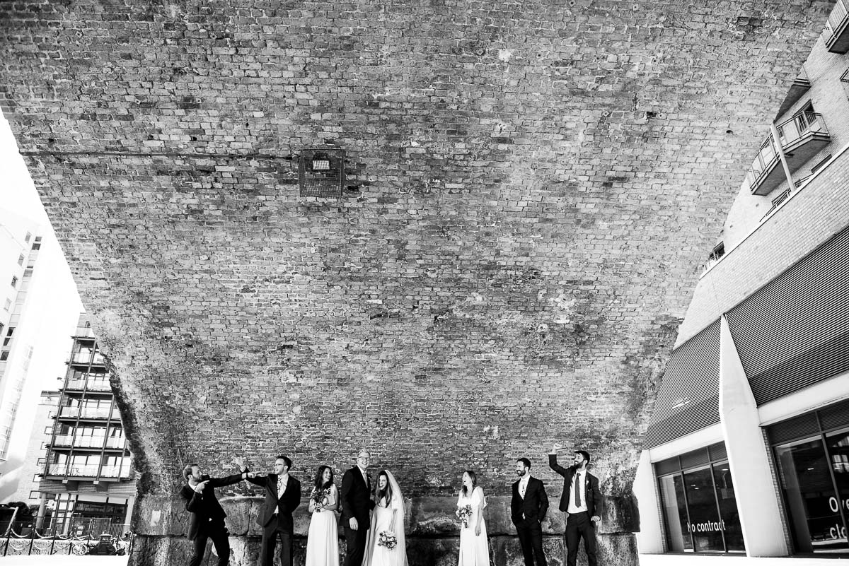 bridesmaids and groomsmen pose under large London bridge