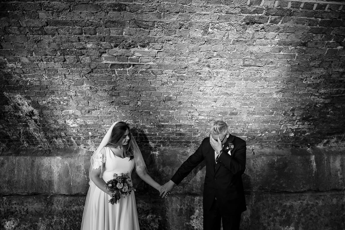 bride and groom holding hands under London bridge