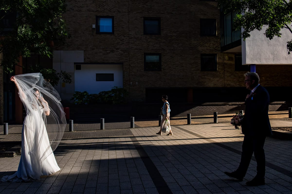 bride plays with her veil in the wind as light falls