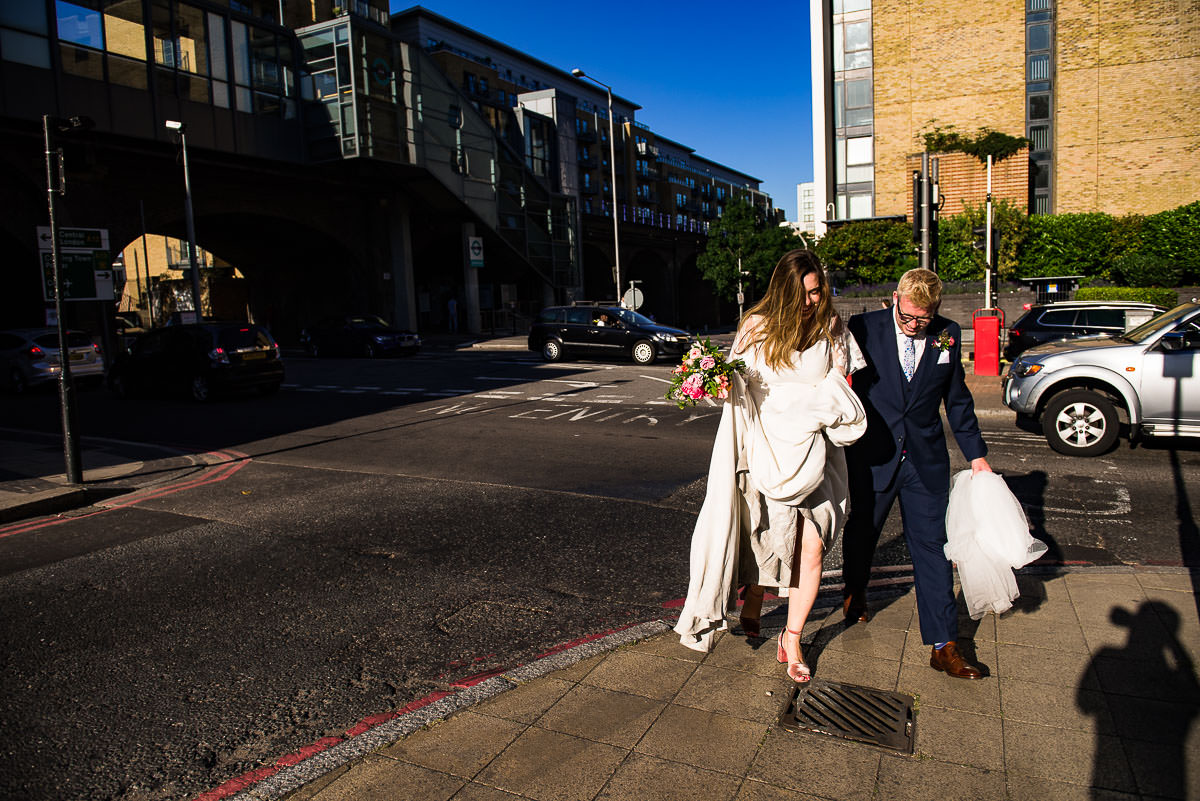 bride carries her dress as she strolls through the streets of London