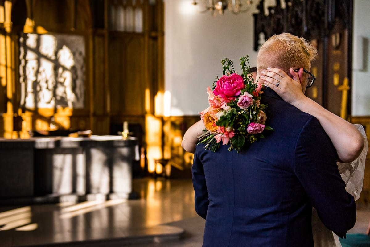bride and groom in London church holding bouquet by wild renata flowers
