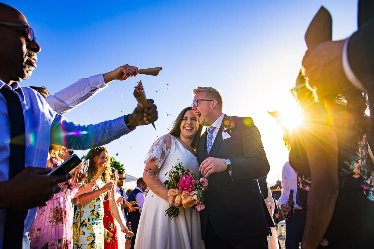 Bride and groom confetti shower as sun sets in London