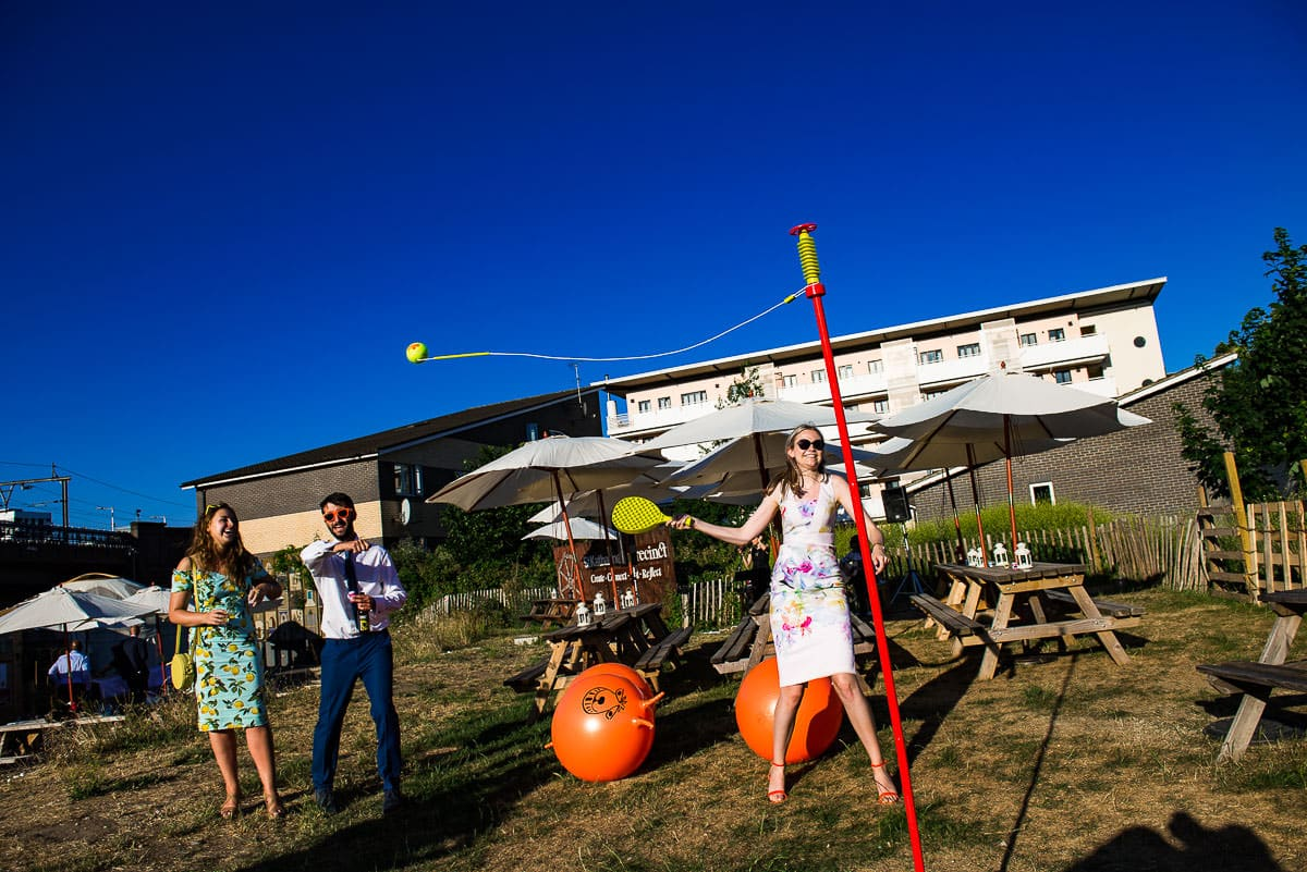 wedding guests enjoy a game of swing ball in the sun in London