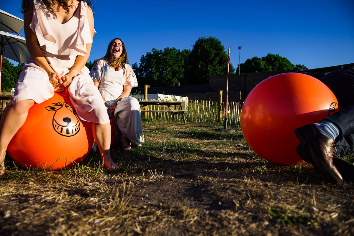 wedding guests race each other on the space hoppers