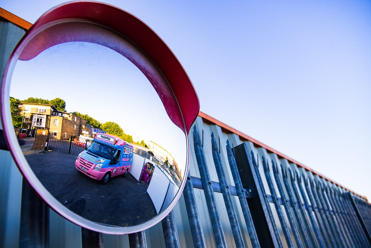 reflection of pink and blue ice cream van in corner mirror