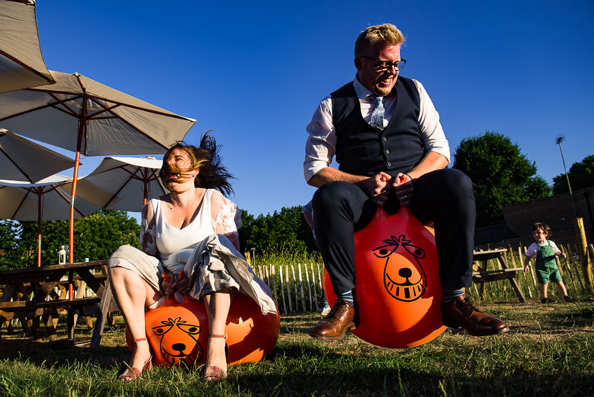 bride and groom bounce on the space hoppers quirky London wedding
