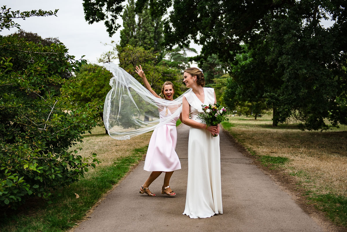 Bride's veil being thrown into the wind as she poses on pathway in park