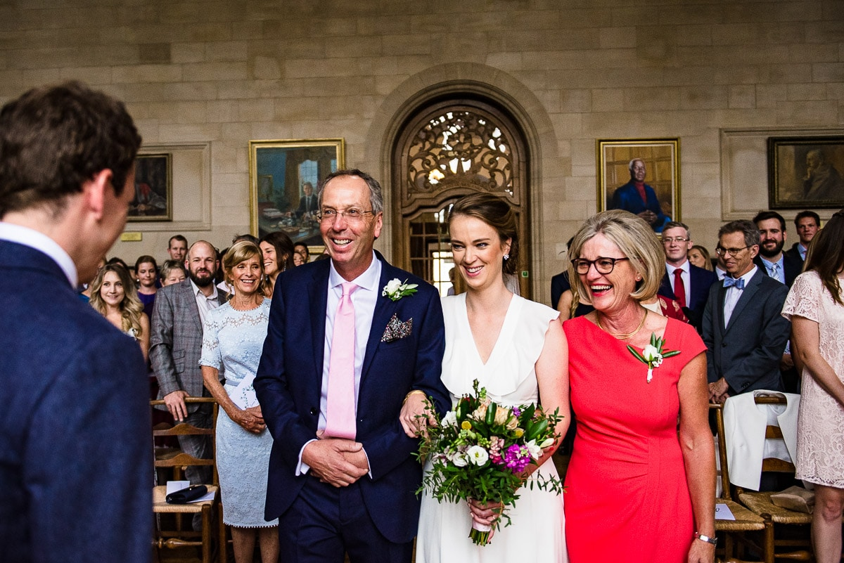 Bride walks down the aisle in the ceremony room with her parents at Rhodes House