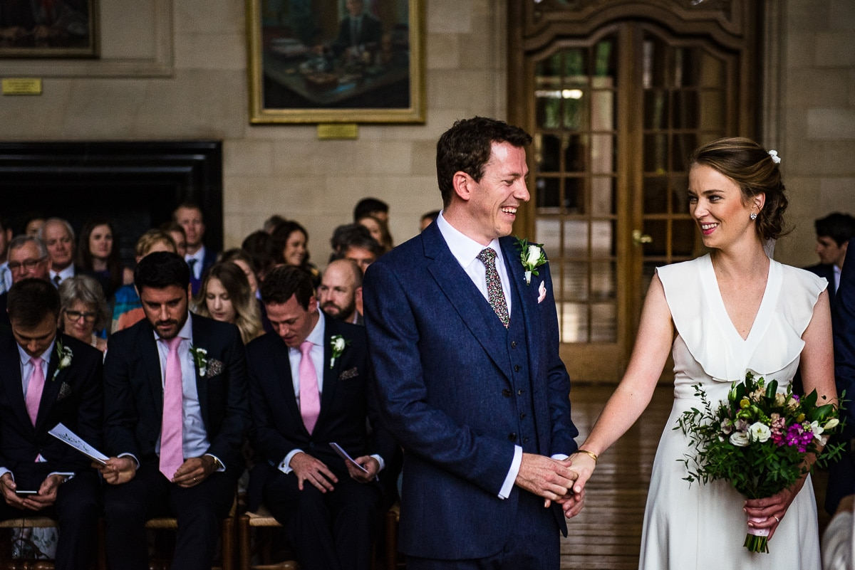 Bride and groom touch hands during wedding ceremony at Rhodes House in Oxford