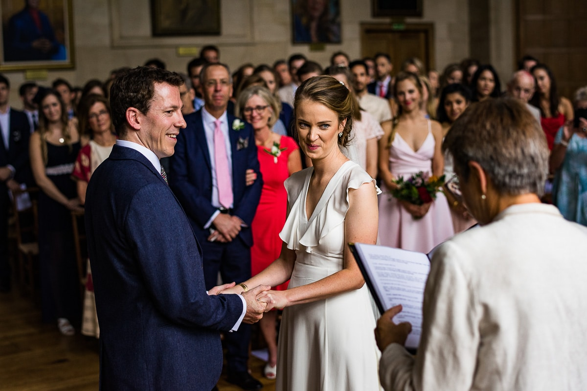 Bride and groom saying vows during wedding ceremony at Rhodes House in Oxford