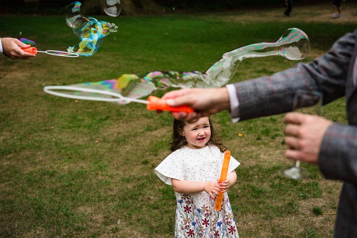 Young girl watches guests make bubbles in garden at Rhodes House photo