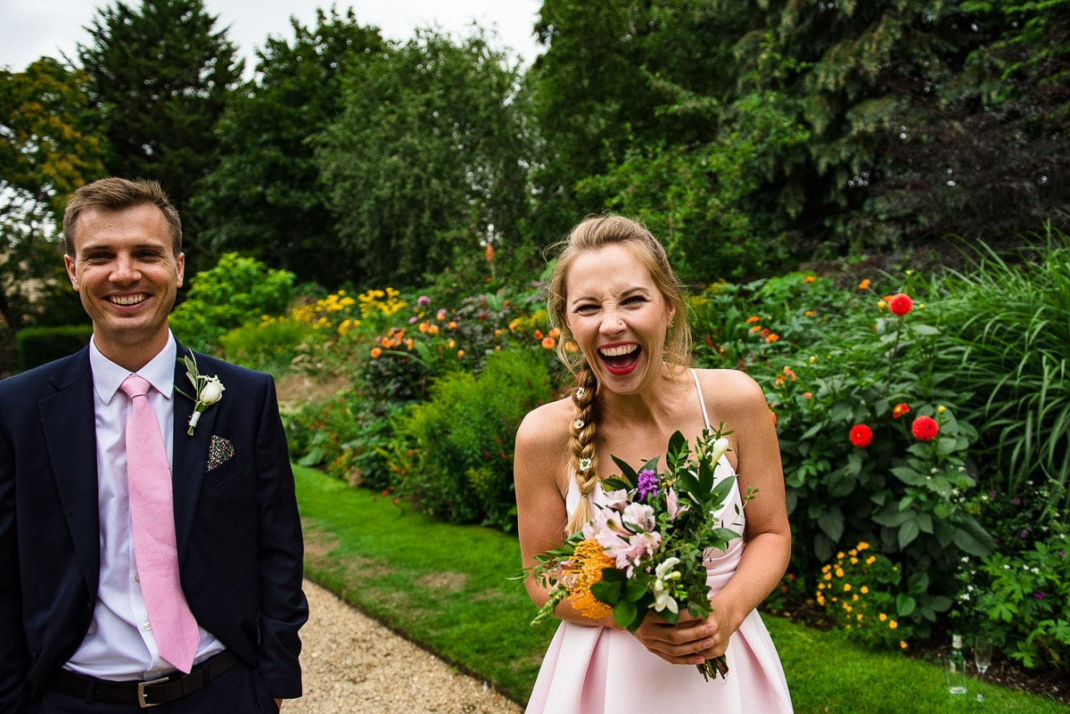 Bridesmaid laughing hysterically holding wedding flowers in garden at Rhodes House