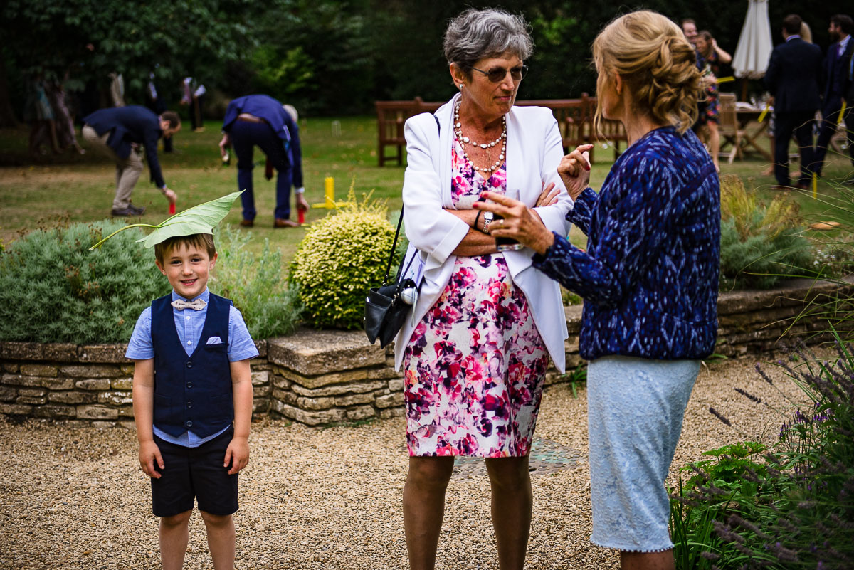 Young page boy with a big leaf on his head in garden of Rhodes House wedding venue Oxford