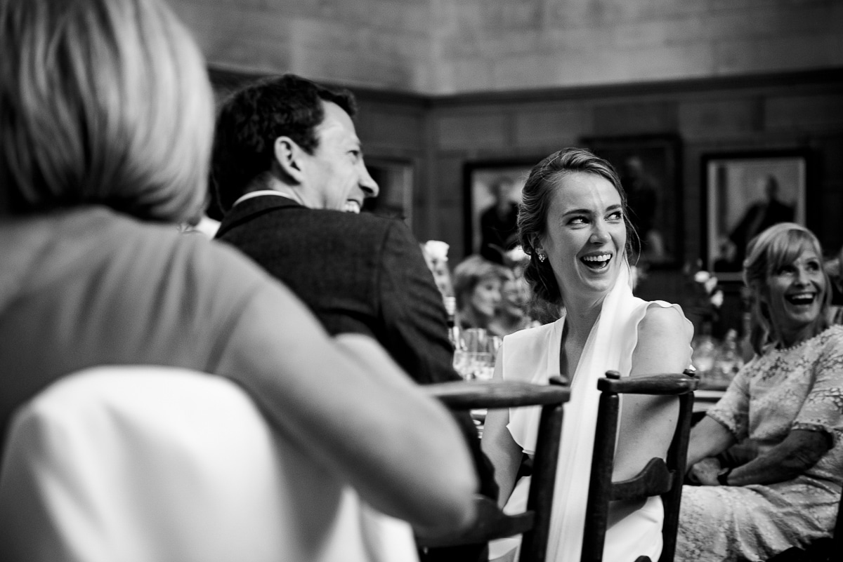 Bride laughing at top table during speeches at Rhodes House Oxford