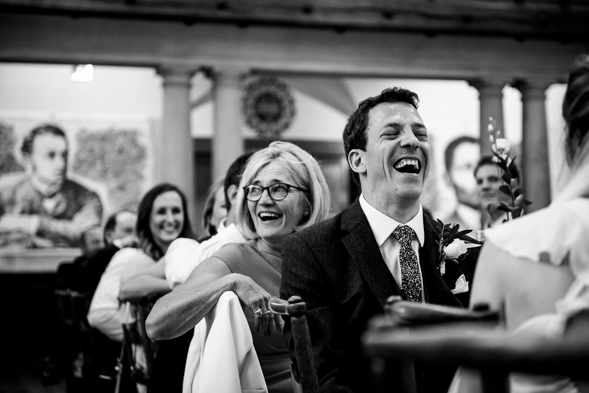 Groom laughing hard during speeches at Rhodes House wedding photo