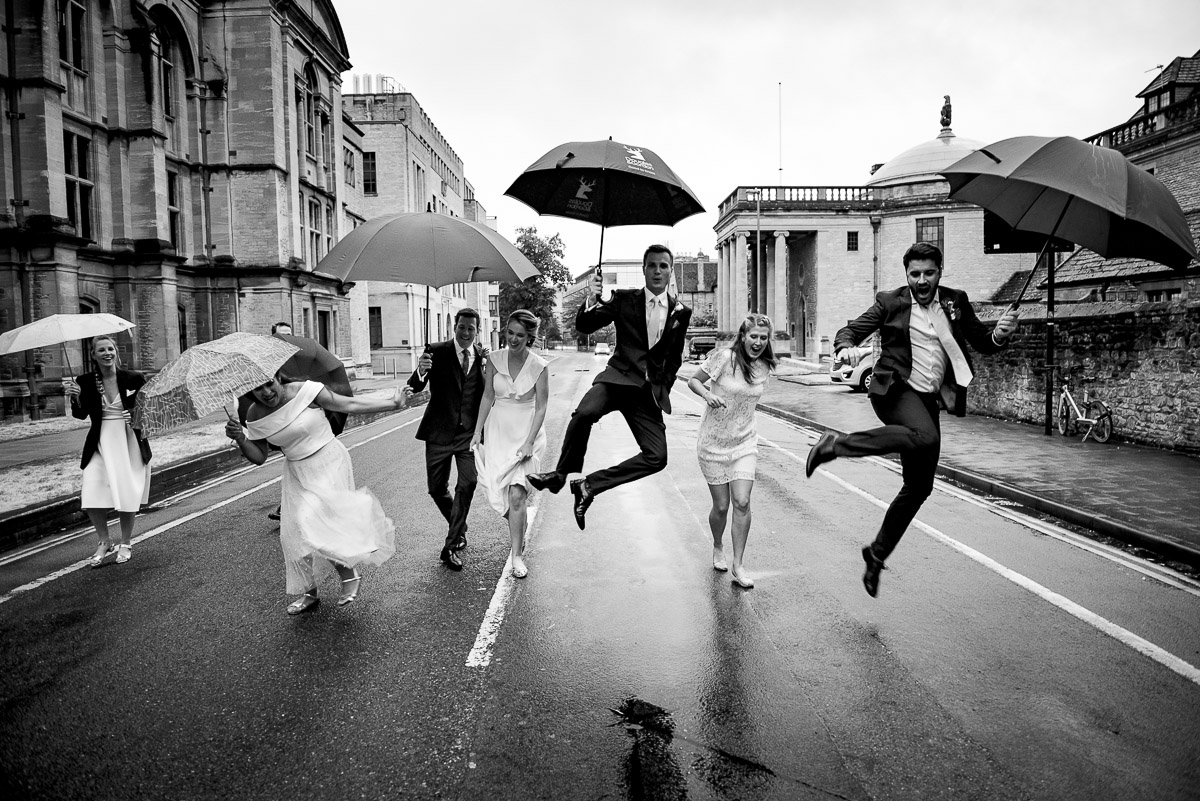 Bridal party jumping with umbrellas on the streets of Oxford photo