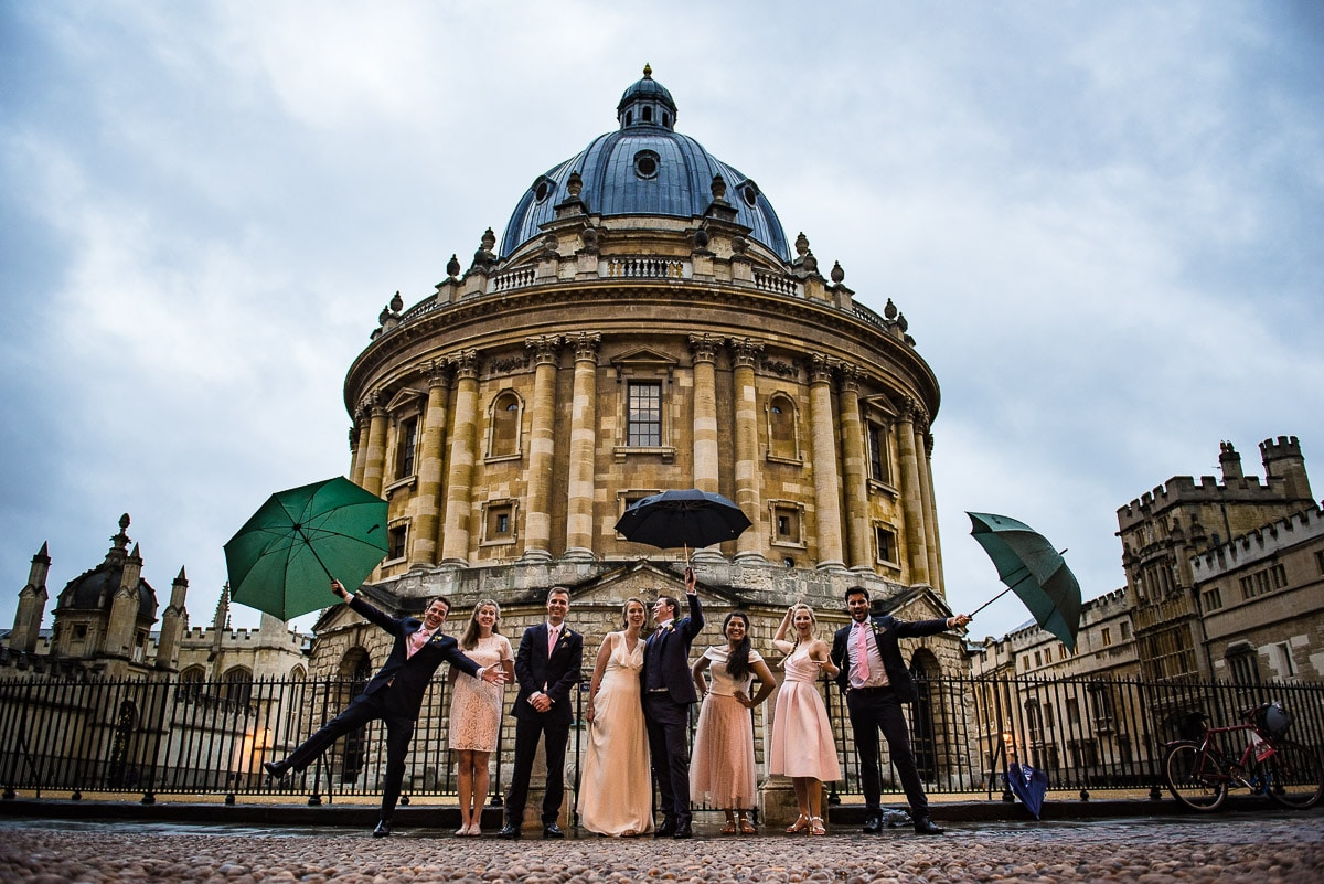 Fun bridal party group photo in the rain on the streets of historic Oxford UK