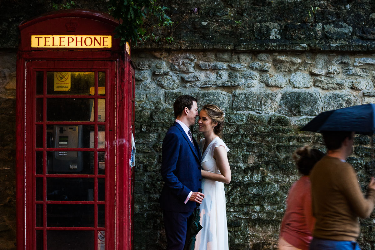 Bride and groom embrace next to a red telephone box in Oxford as tourists walk by